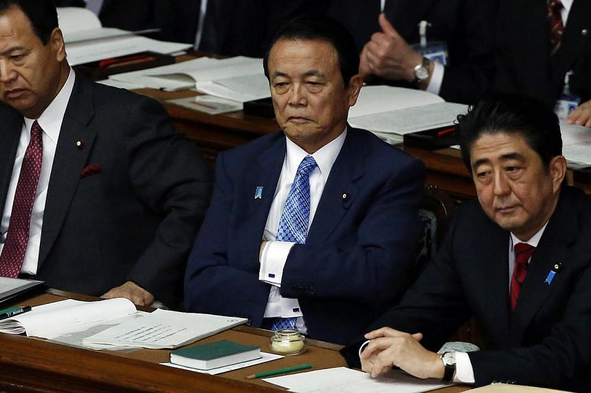 Japan's Prime Minister Shinzo Abe (right), Japan's Deputy Prime Minister and Finance Minister Taro Aso (centre) and Japan's Economics Minister Akira Amari sit at the lower house of the parliament in Tokyo on Jan 24, 2014. Prime Minister Shinzo A