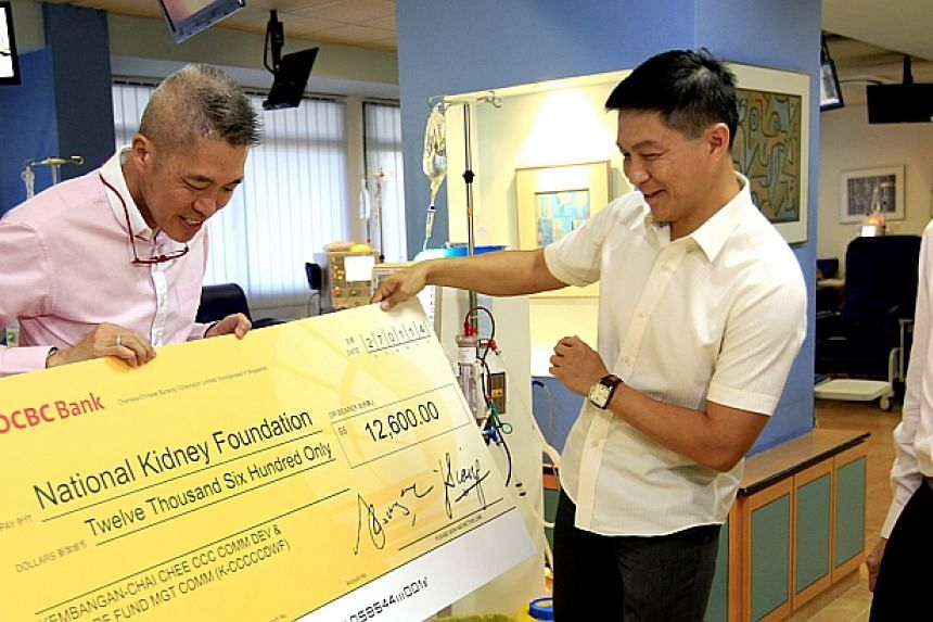 Acting Minister for Manpower, Tan Chuan Jin (centre) looking at the mock-uo cheque after presenting to NKF CEO, Edmund Kwok (left) while Prof Teo Cheng Swee looks on.Kembangan-Chai Chee Citizens' Consultative Committee (CCC) has donated $12,600 to th