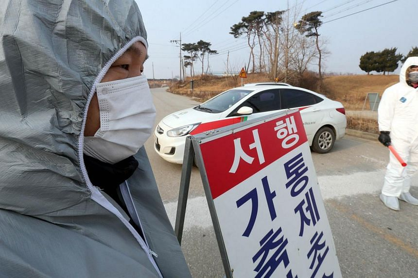 South Korean quarantine officials man a checkpoint near a poultry farm, where a suspected case of avian influenza was reported, in Gochang in North Jeolla Province, some 300km south-west of Seoul, on Jan 17, 2014. South Korea imposed on Monday a 12-h