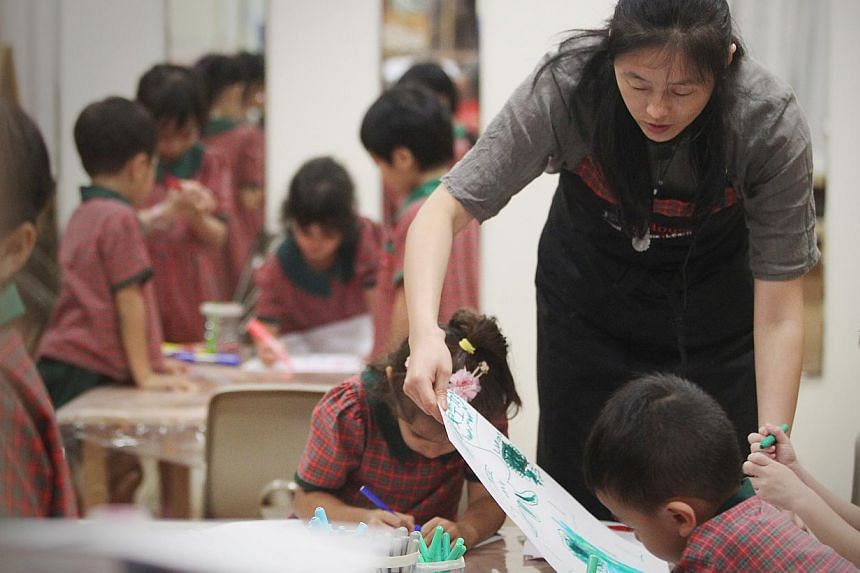 An EtonHouse teacher conducting an art lesson. Amid the push to build more childcare centres, the new pre-school anchor operators said they face the common problem of finding enough qualified teachers. -- ST PHOTO: JASON QUAH