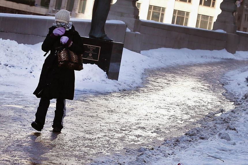 A pedestrian navigates an ice-covered sidewalk along the Chicago River as temperatures drop below zero in Chicago, Illinois, on Jan 27, 2014. -- PHOTO: AFP