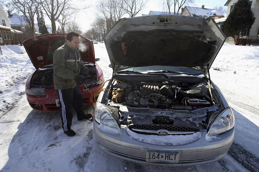 Mr Javier Arias coils up starter cables as he successfully jump starts his car after charging the battery for 30 minutes in Minneapolis on Jan 27, 2014. -- PHOTO: REUTERS