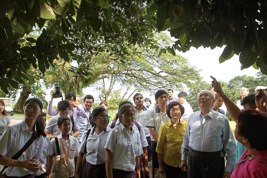 President Tony Tan Keng Yam (foreground, second from right) and Mrs Mary Tan (in yellow) join some 30 people, including students from Cedar Primary School, Queenstown Secondary School and West Spring Secondary School, as well as beneficiaries from th