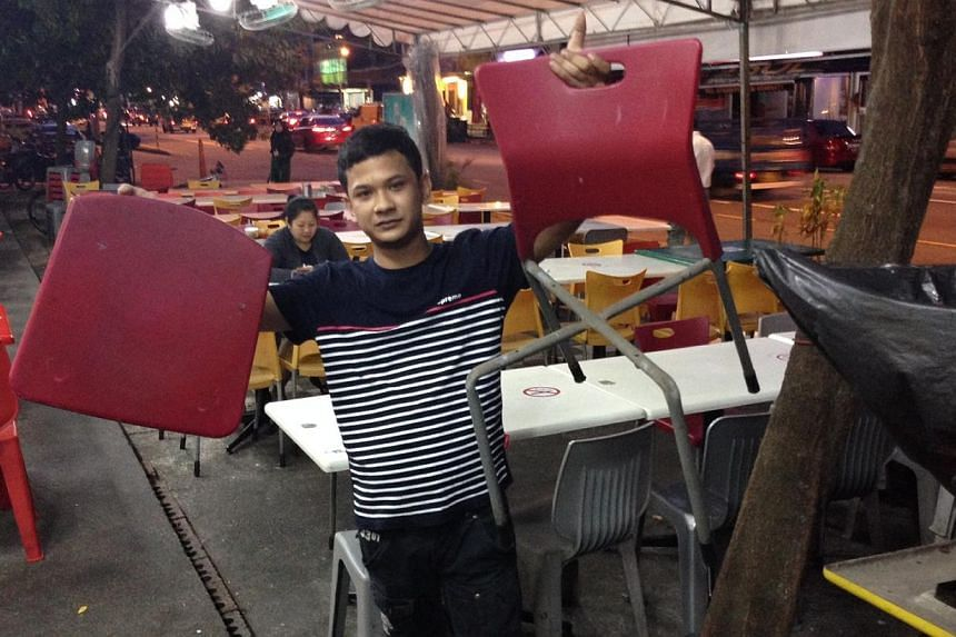 New Hawa's coffeeshop assistant Muhammad Abdul Qadir Abdul Malek Al, 22, holding up one of the six chairs that were broken by the man. Manager Mr Chew Kee How, 61, said that the damages amounted to about $100. -- ST PHOTO: YEO SAM JO