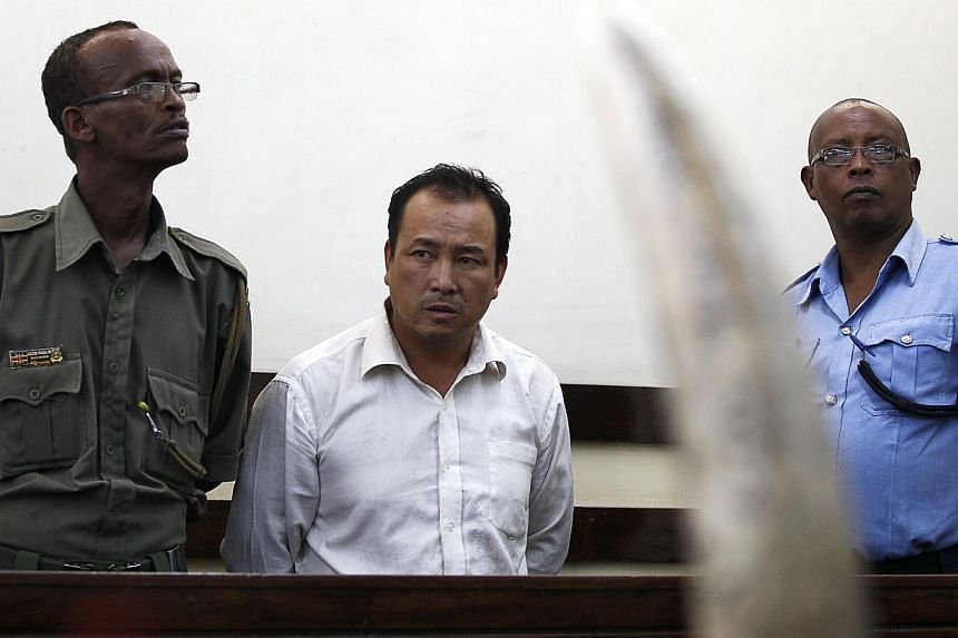 Tang Yong Jian (centre), a Chinese national, stands guarded inside the dock at the Makadara Law courts in Kenya's capital Nairobi, Jan 28, 2014. A court in Kenya on Tuesday slapped a record sentence on a Chinese ivory smuggler, the first person to be