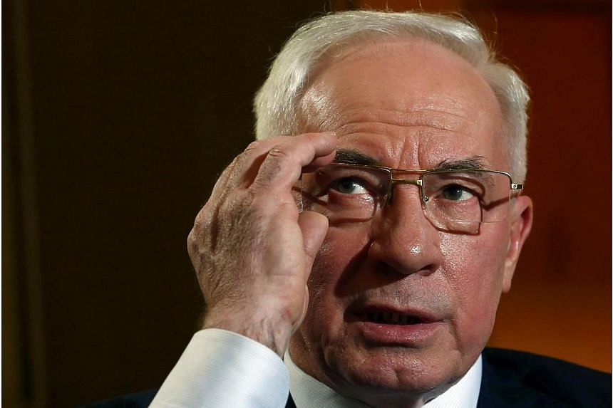 Ukrainian Prime Minister Mykola Azarov adjusts his glasses during an interview with Reuters at the annual meeting of the World Economic Forum (WEF) in Davos, on Jan 23, 2014.Prime Minister Mykola Azarov resigned on Tuesday, Jan 28, 2014, in a b