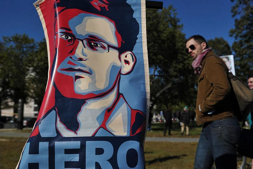 """Portrait of Edward Snowden declaring him a """"hero"""" during a protest against government surveillance in Washington, DC,on Oct 26, 2013.An internet campaign calling for US intelligence leaker Edward Snowden to be granted asylum in Brazil has"""