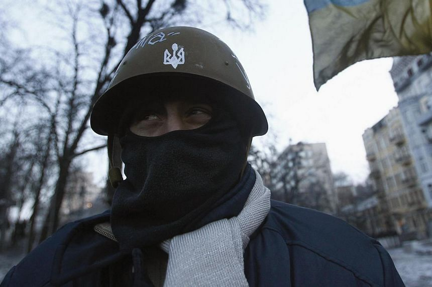 An anti-government protester looks out from a barricade at the site of clashes with police in Kiev, on Jan 27, 2014. They stood like a unit from a paramilitary army, in camouflage fatigues and clutching baseball bats, their faces concealed underneath