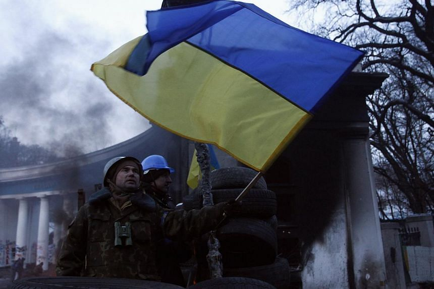 An anti-government protester flies a Ukrainian flag from barricades at the site of clashes with police in Kiev on Jan 27, 2014. -- PHOTO: REUTERS