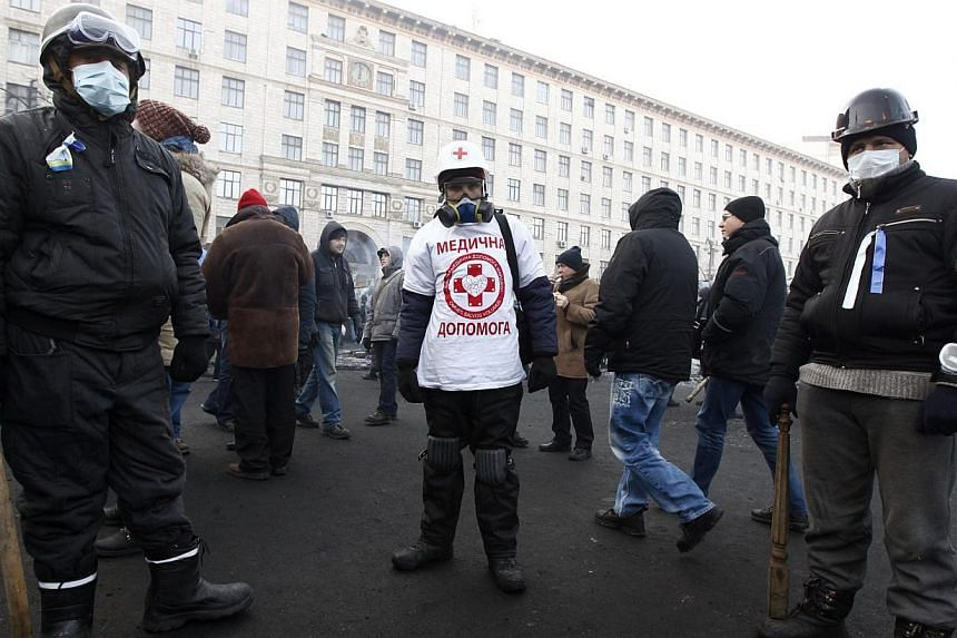 A medical volunteer stands between anti-government protesters at the site of clashes with riot police in Kiev on Jan 27, 2014. -- PHOTO: REUTERS