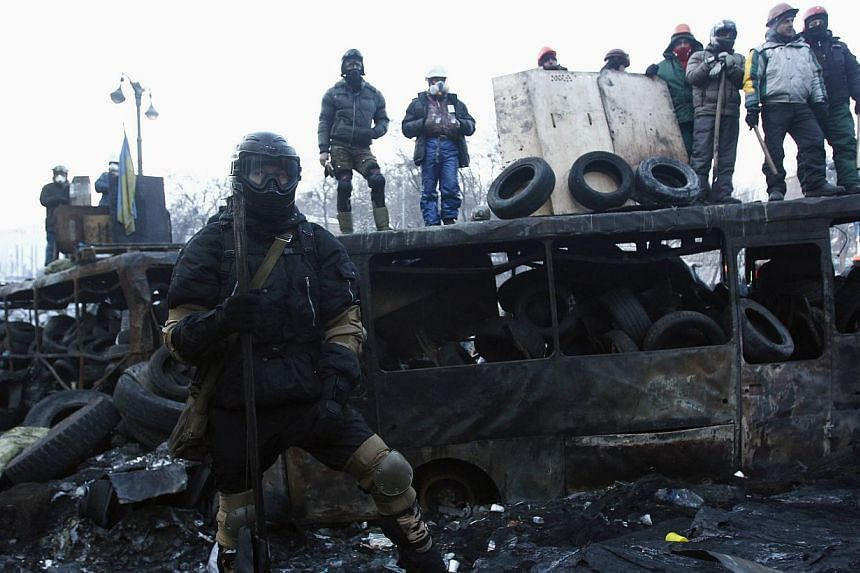 Anti-government protesters look out from barricades at the site of clashes with police in Kiev on Jan 27, 2014. -- PHOTO: REUTERS
