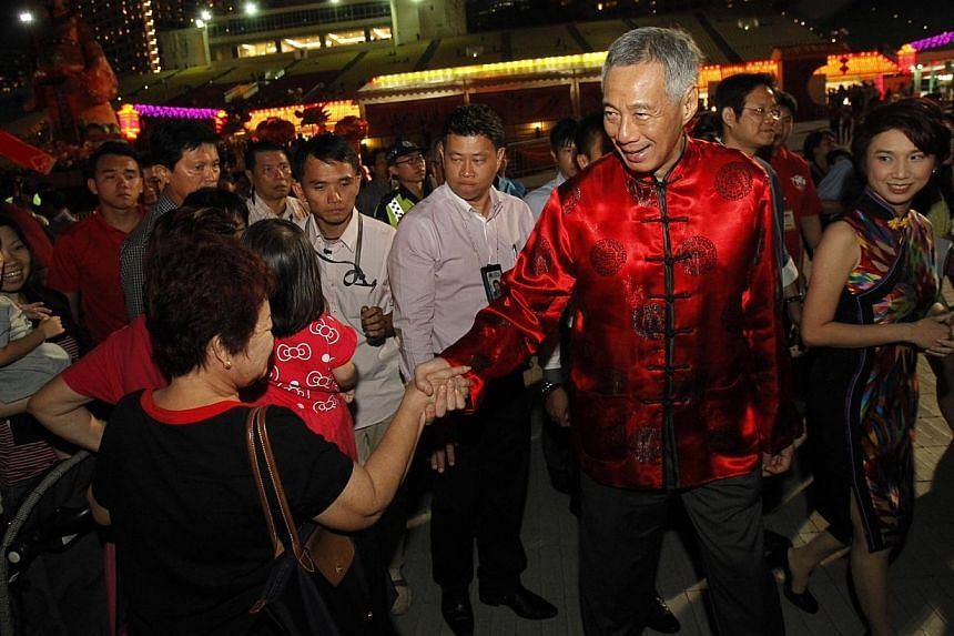 Prime Minister Lee Hsien Loong shakes hands with those present upon his arrival at the River Hongbao opening ceremony at on Jan 29, 2014. -- ST PHOTO: KEVIN LIM