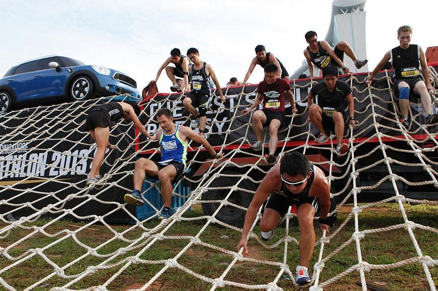 Road warriors in last year's Men's Health Urbanathlon tackling the Network, climbing up the rope web and then descending feet first while avoiding getting caught in the net, a task obviously tougher than corporate networking.  Singapore runner Anne Q