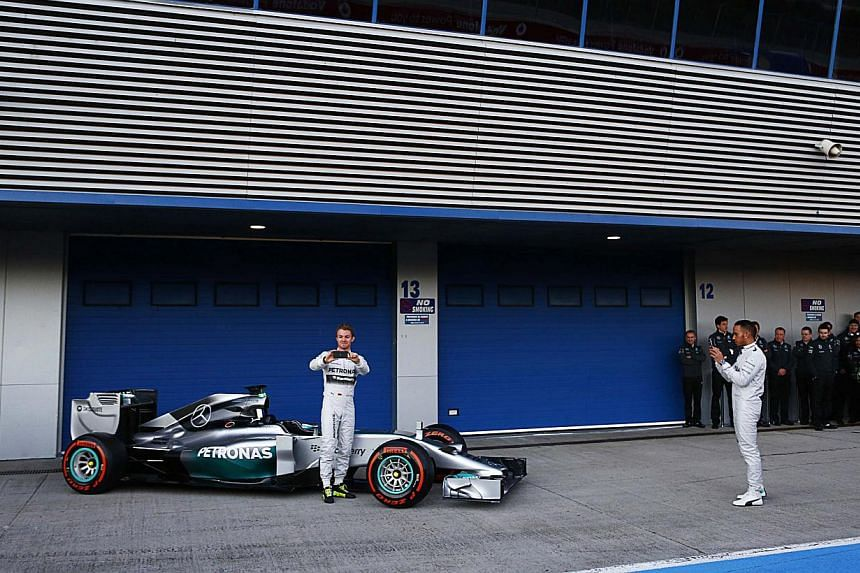 Mercedes Formula One racing driver Lewis Hamilton (right) of Britain and teammate Nico Rosberg of Germany take part in the official presentation of the new Mercedes F1 W05 car at the Jerez racetrack in southern Spain on Jan 28, 2014.The sound o