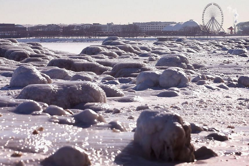 A Ferris wheel on Navy Pier rises above ice along the shore of Lake Michigan in Chicago, Illinois, on Jan 28, 2014.A rare blast of snow, sleet and ice hit the United States South on Tuesday, prompting residents accustomed to more moderate weath