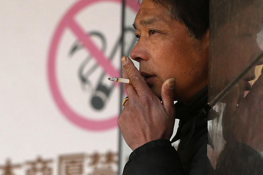 """A man smokes in front of a """"no smoking"""" sign outside a shopping mall in Shanghai on Jan 10, 2014.China has banned smoking in schools, state media reported on Wednesday, the latest step in a government drive to kick the country's pervasive tobac"""