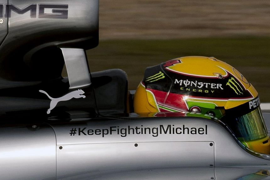 Mercedes AMG Petronas' British driver Lewis Hamilton drives the new Mercedes W05 displaying a message of support for seven-time World Champion Michael Schumacher during the Formula One pre-season test days at Jerez racetrack in Jerez on Jan 28, 2014.