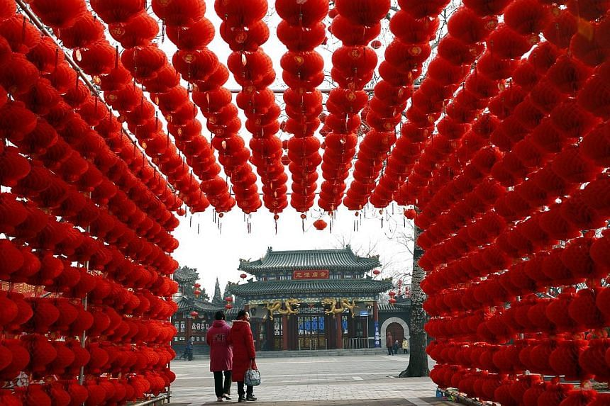 Visitors walking past red lantern decorations at Longtan park ahead of the upcoming Chinese lunar New Year in Beijing on January 29, 2014. -- PHOTO: REUTERS