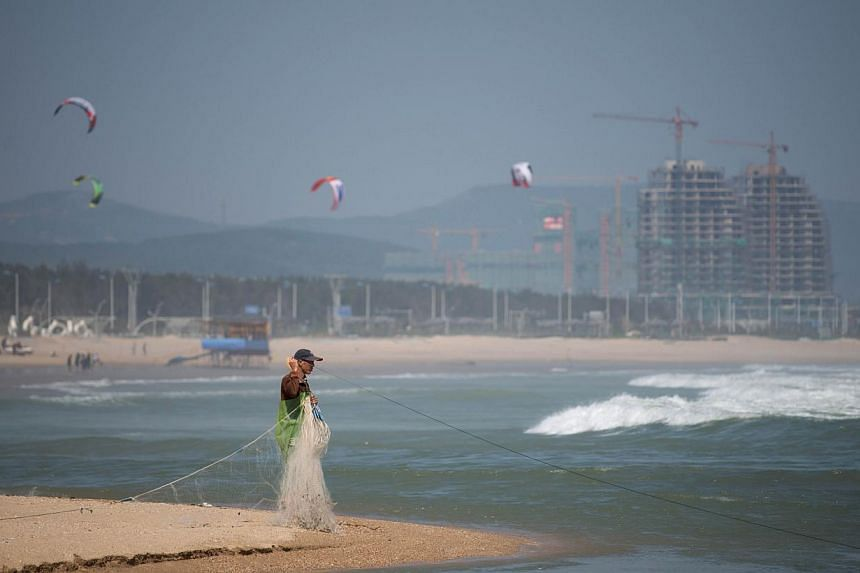 This photo taken on October 24, 2013 shows a fisherman hauling his net as he stands on a beach on the island of Pingtan, in China's south-eastern Fujian province. Pingtan island is physically China's closest spot to Taiwan, and is now also being tran