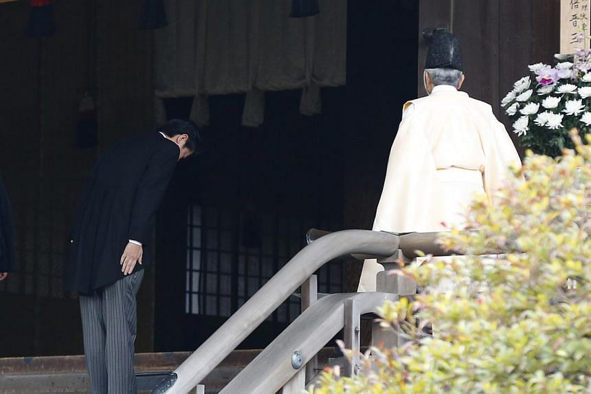 Japan's Prime Minister Shinzo Abe bowing beside a Shinto priest as he visits the Yasukuni shrine in Tokyo on December 26, 2013. -- FILE PHOTO: REUTERS