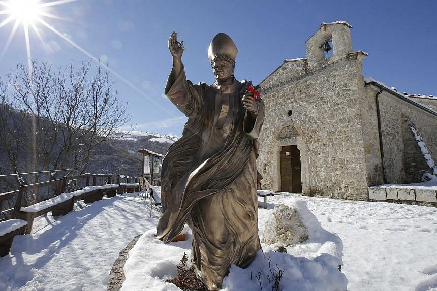 A statue of the late Pope John Paul II is seen in front of the small mountain church of San Pietro della Ienca, near the city of L'Aquila, on Jan 28, 2014 .Thieves broke into the small church in the mountains east of Rome over the weekend and stole t