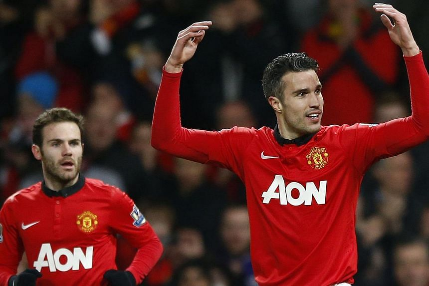 Manchester United's Juan Mata (left) looks on as teammate Robin van Persie celebrates scoring against Cardiff City during their English Premier League soccer match at Old Trafford in Manchester on Jan 28, 2014. Van Persie and Ashley Young scored as M
