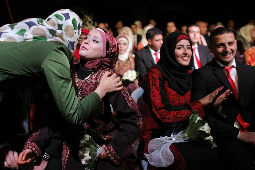 A relative congratulates a Palestinian bride during a mass wedding ceremony in the West Bank city of Jericho on Jan 28, 2014.Nearly 600 Palestinians were married in the West Bank and the Gaza Strip on Tuesday in a mass wedding funded by the Wes