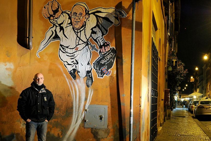 """Italian street artist Maupal poses next to his street art mural of Pope Francis as a superman, flying through the air with his white papal cloak billowing out behind him and holding a bag bearing the word """"Values"""", in downtown Rome near the Vatican,"""