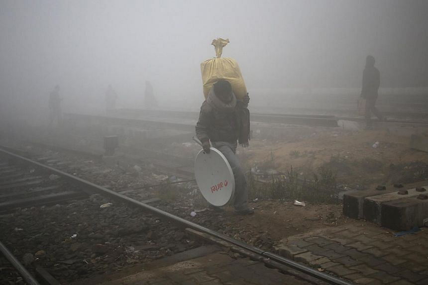 People cross railway tracks on a foggy winter morning in New Delhi Dec 18, 2013.India's air monitoring centre denied on Wednesday that pollution in New Delhi was worse than in Beijing, following scrutiny of the Indian capital's winter smog, whi