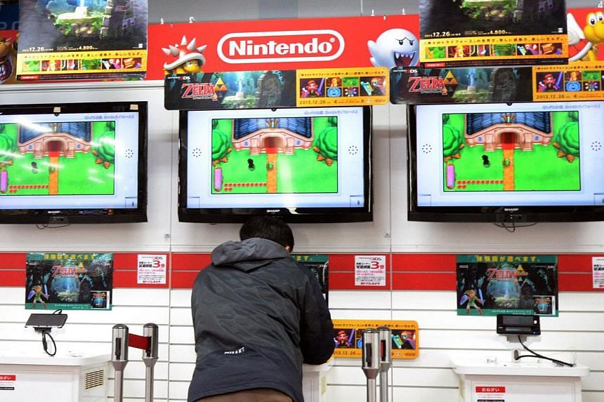 A man plays Nintendo's portable video game console at an electronic shop in Tokyo on Jan 17, 2014. Japan's Nintendo said on Wednesday that nine-month profit dived 30 per cent on slumping demand for its Wii U games console, and warned again that it wo