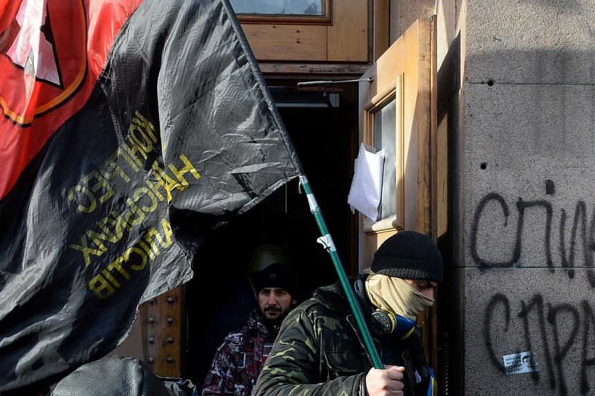 Activists from the radical Spilna Sprava (Common Cause) leave the agriculture ministry building they had occupied for several days, following clashes with representatives of right wing Ukraine opposition party Svoboda (Freedom) in Kiev, on Wednesday,