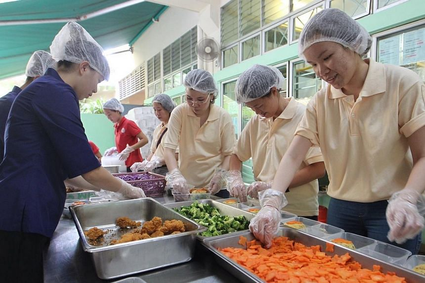 Staff of the Soup Restaurant help to pack the food prepared by Thye Hua Kwan Moral Welfare Home's kitchen to be delivered to the homes of several elderly clients. -- ST PHOTO: NEO XIAOBIN