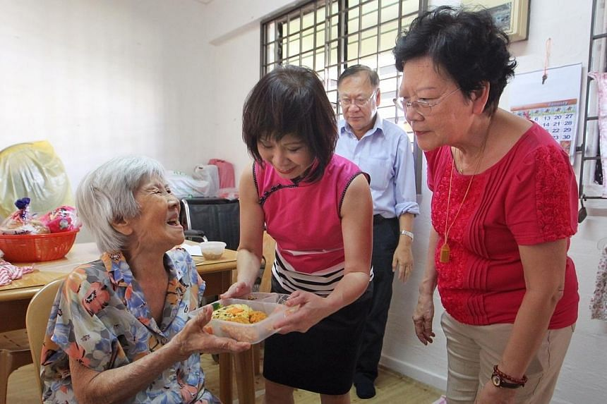 Madam Kwok Mun Yin (extreme left) reacts as Mayor of South West District Dr Amy Khor (in pink) passes her the food prepared by Thye Hua Kwan Moral Welfare Home's kitchen, as well as mandarin oranges and an ang bao. -- ST PHOTO: NEO XIAOBIN
