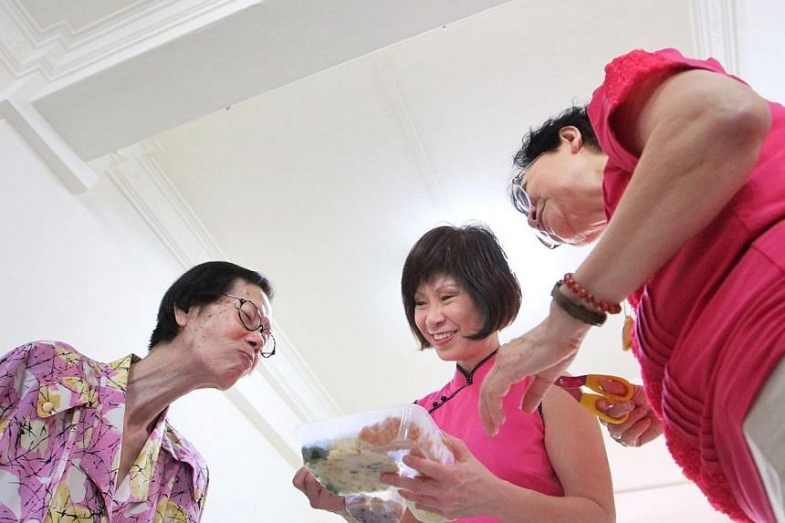 Madam Foong Kim Geok (extreme left) takes a sniff as Mayor of South West District Dr Amy Khor (in pink) passes her the food prepared by Thye Hua Kwan Moral Welfare Home's kitchen, as well as mandarin oranges and an ang bao. -- ST PHOTO: NEO XIAO