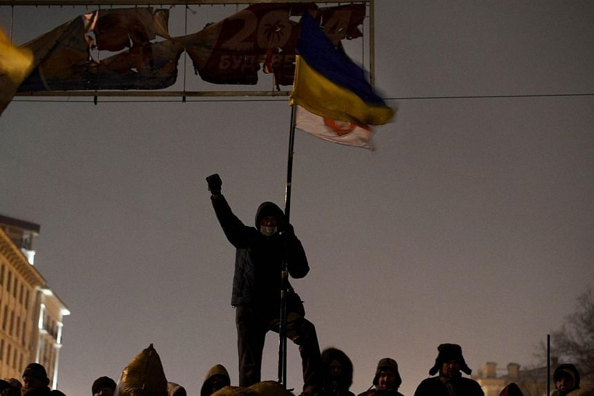 "A demonstrator raises his fist as anti-government protesters gather at a road block in Kiev, on Jan 28, 2014. Ukraine is on the brink of ""civil war"" due to the standoff between the authorities and protesters across the country, its first post-in"