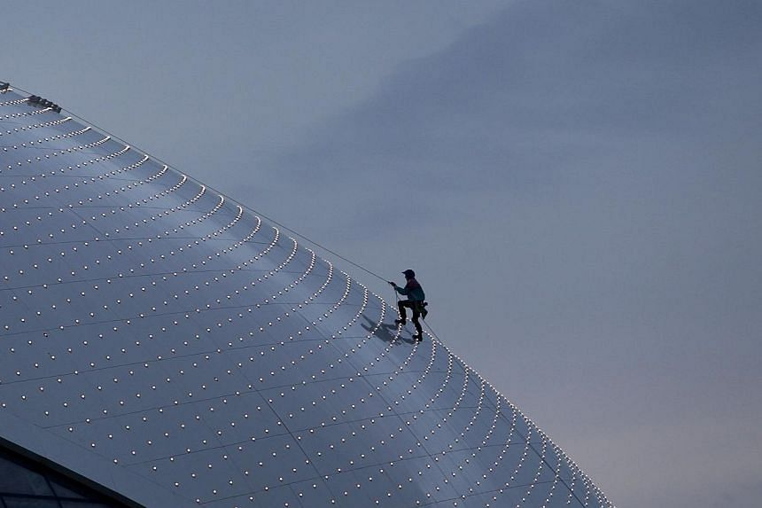 A workman climbs up the roof of the Bolshoy Ice Dome as preparations continue at the Olympic Park for the Sochi 2014 Winter Olympics, Jan 28, 2014. The Bolshoy Ice Dome will host the Olympic ice hockey competition. -- PHOTO: REUTERS