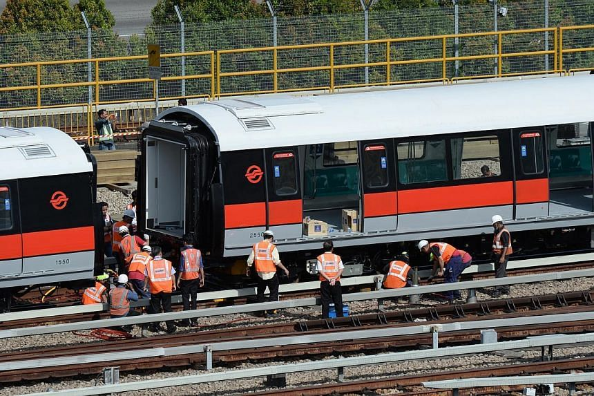 Workers inspecting one of the carriages that derailed at the Bishan Depot yesterday. No passengers were on board and there were no injuries. -- ST PHOTO: JOYCE FANG
