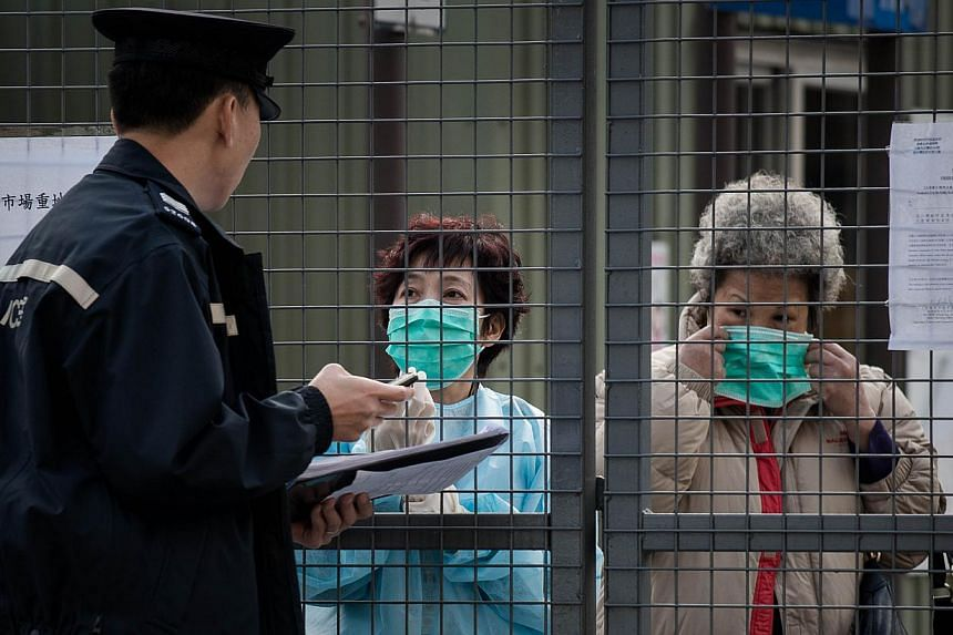 A policeman talks to employees of a wholesale market where infected poultry imported from mainland China was discovered in Hong Kong, on Jan 28, 2014. A recent outbreak of bird flu in China has cost poultry farmers 20 billion yuan (S$4.2