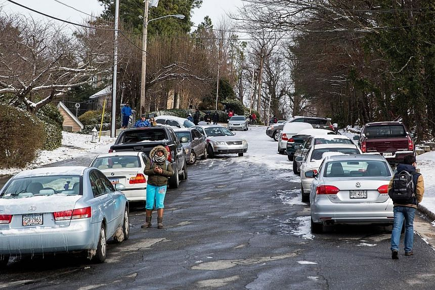 People try to retrieve their abandoned vehicles that line a street during the winter storm in Atlanta, Georgia, on Jan 29, 2014. -- PHOTO: AFP