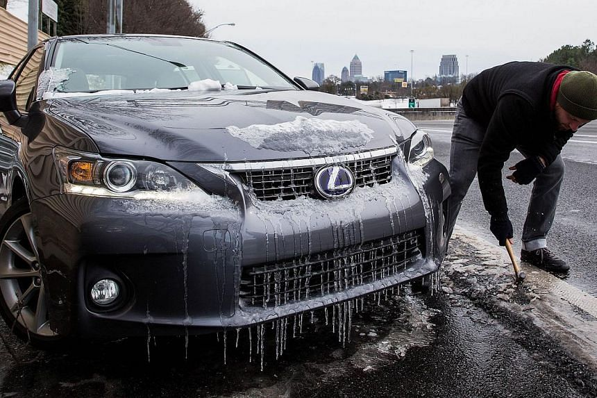 Joe Galunas works to clear ice and retrieve the car he abandoned on an exit ramp along I-75 North during the winter storm in Atlanta, Georgia, on Jan 29, 2014. -- PHOTO: AFP