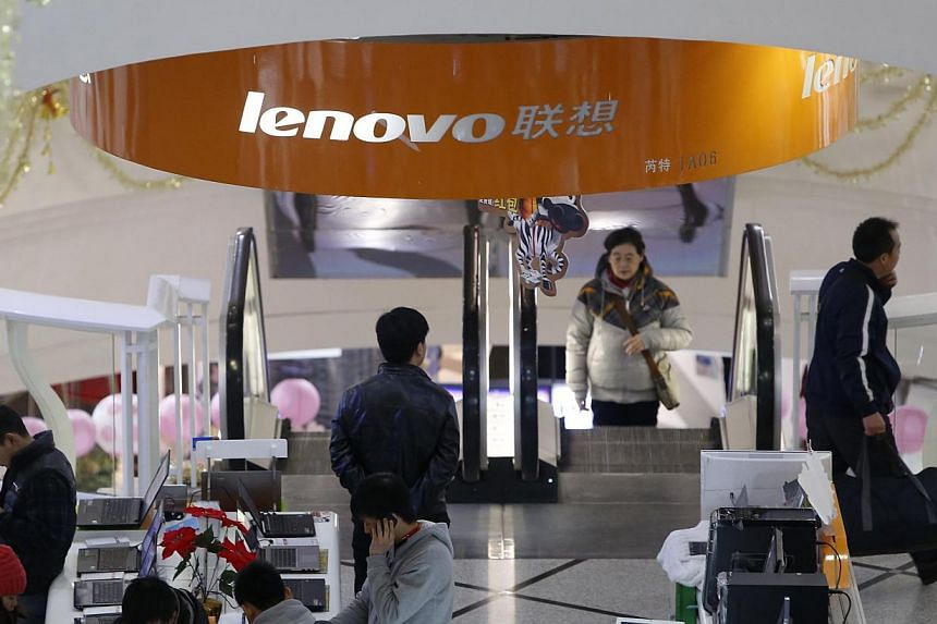 People stand under a sign showing the Lenovo company at a computer market in Shanghai on Jan 21, 2014. China's Lenovo Group is nearing a deal to buy Google Inc's Motorola handset division for close to US$3 billion (S$3.8 billion), people familiar wit