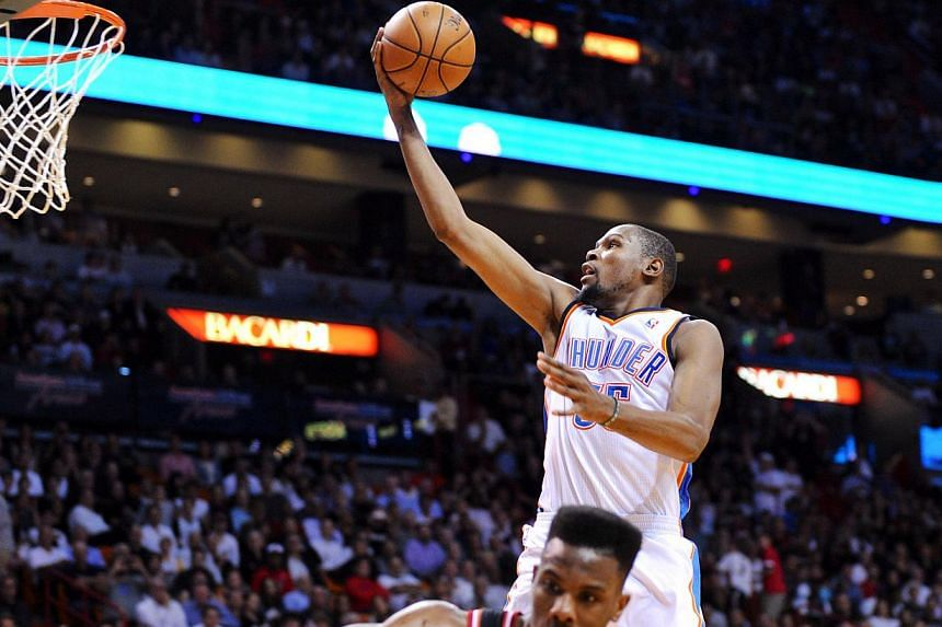 Oklahoma City Thunder small forward Kevin Durant (35) dunking past Miami Heat point guard Norris Cole during the first half at American Airlines Arena. Oklahoma City Thunder dominated the Miami Heat 112-95 on Wednesday. -- PHOTO: REUTERS
