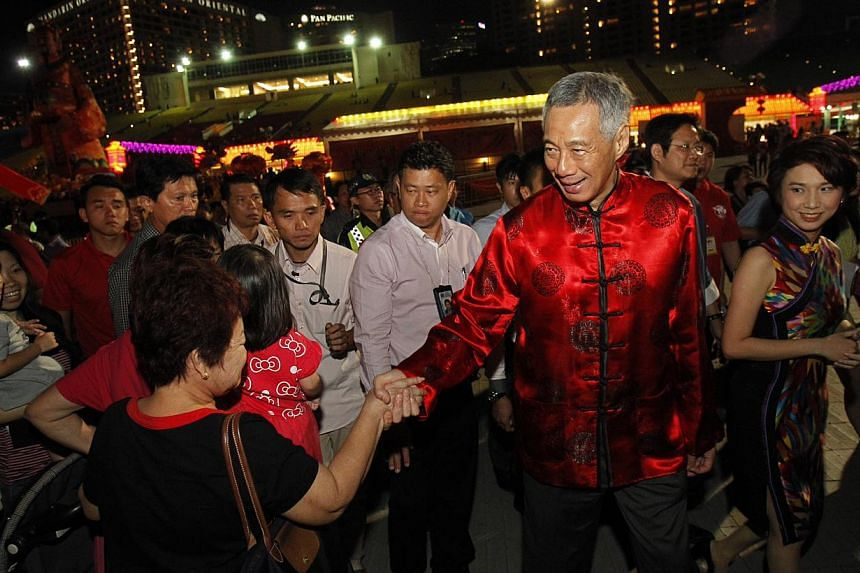 """Prime Minister Lee Hsien Loong shakes hands with those present upon his arrival at the River Hongbao opening ceremony on Jan 29, 2014. As families gather for their reunion dinner tonight, Singapore's elderly can look forward to a """"little hongbao"""" fro"""