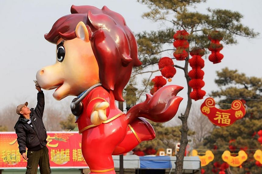 This picture taken on Jan 28, 2014, shows a worker putting the final touches on a cartoon horse at a temple fair in Beijing for the upcoming Lunar New Year, marking the Year of the Horse starting on Jan 31, 2014. -- FILE PHOTO: AFP