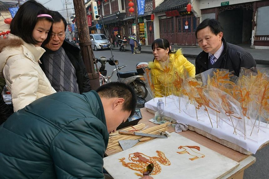 A man makes Chinese Zodiac animals from candy at a Chinese New Year street fair on the eve of the holiday in Shanghai, on Jan 30, 2014. -- PHOTO: AFP