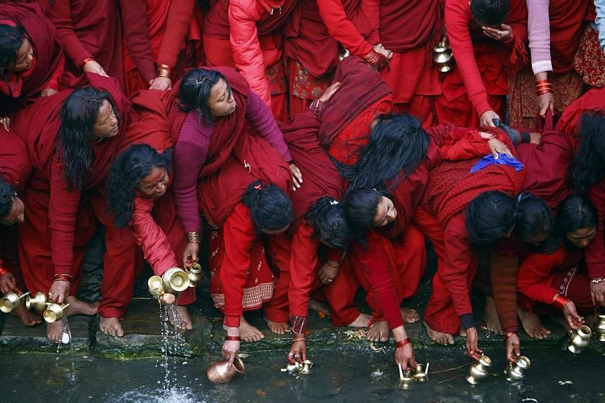Devotees fill their vessels with water, which is considered to be holy, from the Bagmati River at Pashupatinath Temple during the Swasthani Bratakatha festival in Kathmandu on Thursday, Jan 30, 2014. See more pictures from around the world in Through