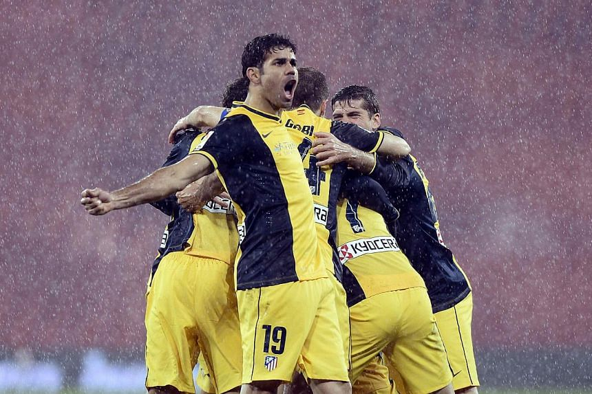 Atletico Madrid players celebrate a goal during their Spanish King's Cup match against Athletic Bilbao at San Mames stadium in Bilbao on Jan 29, 2014. Holders Atletico Madrid set up a mouthwatering Copa del Rey semi-final with city rivals Real Madrid