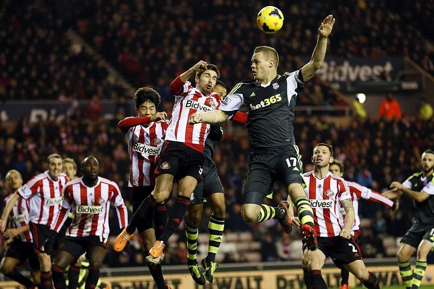Stoke City's Ryan Shawcross (top right) and Sunderland's Fabio Borini fight for the ball during their English Premier League football match at the Stadium of Light in Sunderland, northern England January 29, 2014. Sunderland moved out of the bottom t