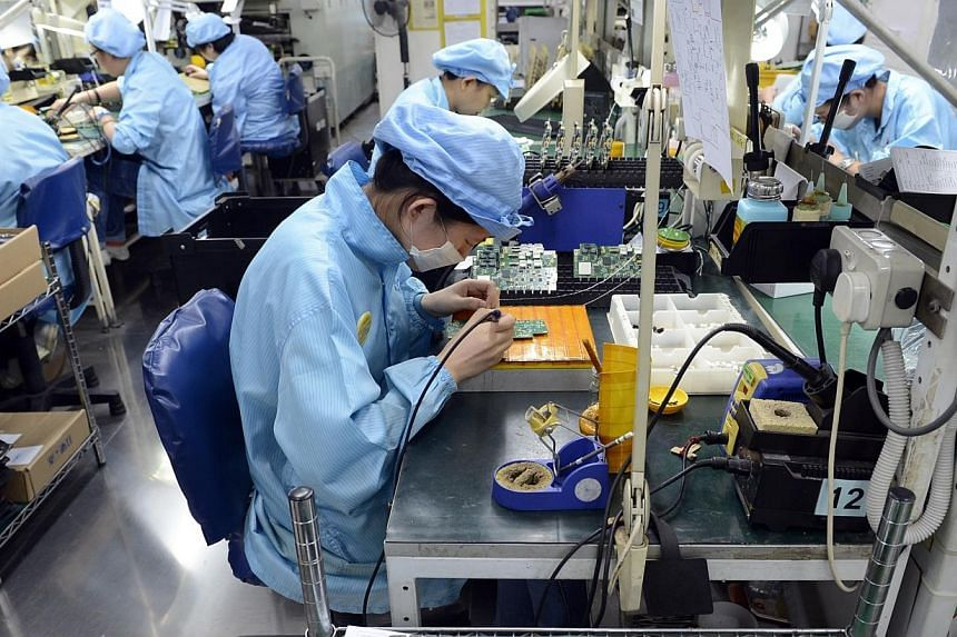 Bosses of manufacturing firms in Singapore have become generally more optimistic about business conditions, on the back of an improving global economy. -- ST FILE PHOTO:DESMOND FOO
