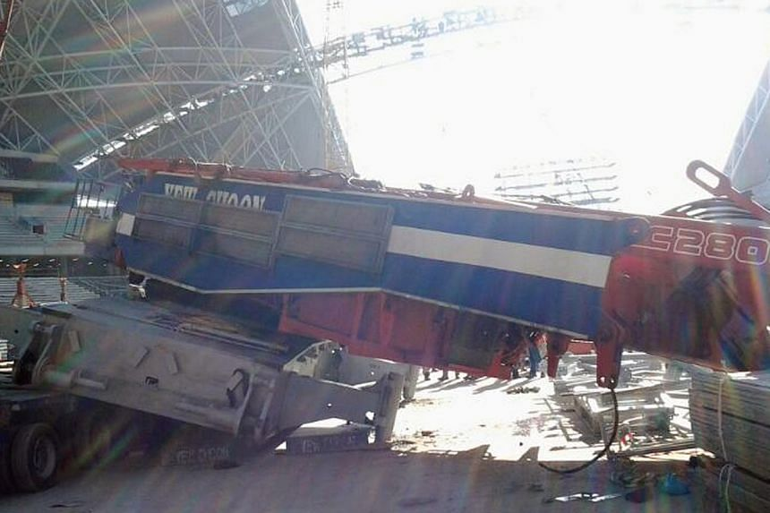 In yet another worksite accident, a 600-tonne crane slid off a trailer on Wednesday afternoon at Kallang, where the new National Stadium is being built. -- PHOTO:STOMP